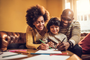 Young African American family having fun while drawing together at home.